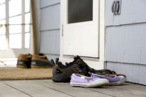 several-pairs-o-shoes-at-the-front-door-next-to-door-matt-725x483