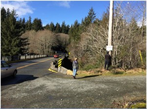 "Posting a new CRD ""No Dumping"" sign at Muir Creek Bridge (photo credit – B. Dushenko)"