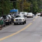 Pedestrian walks between parked and moving cars on West Coast Road. SPN photo.